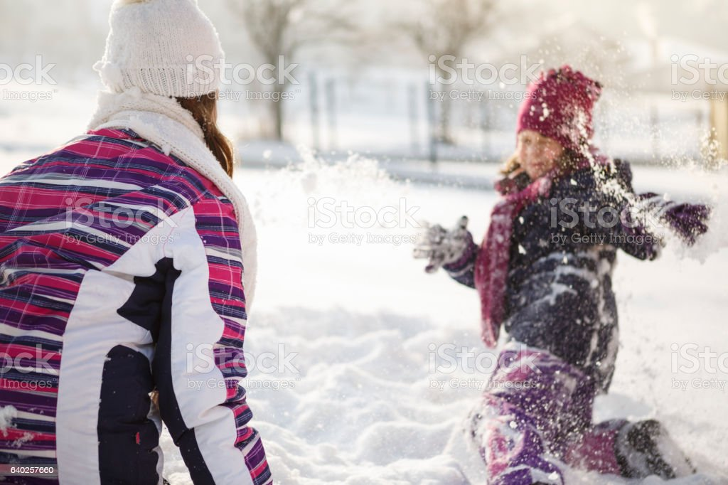 Happy kids playing in snow stock photo