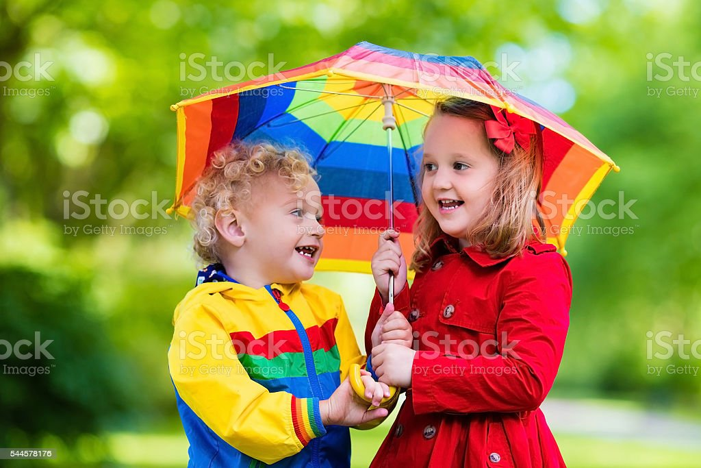 Happy kids playing in the rain under colorful umbrella stock photo