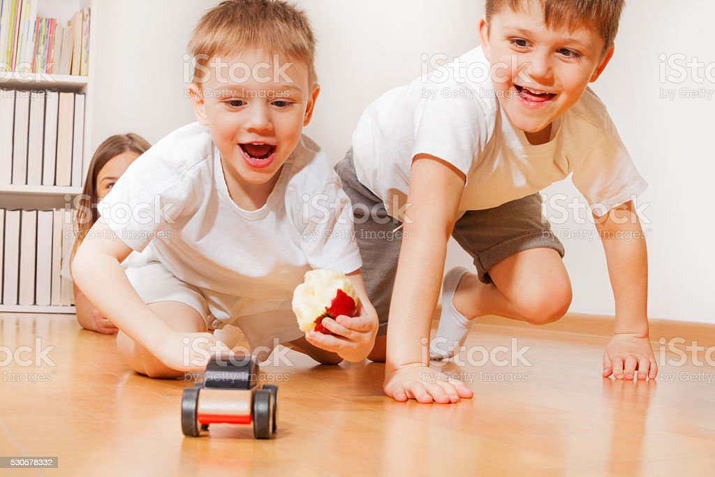 Happy kids playing with wooden toy car at floor stock photo