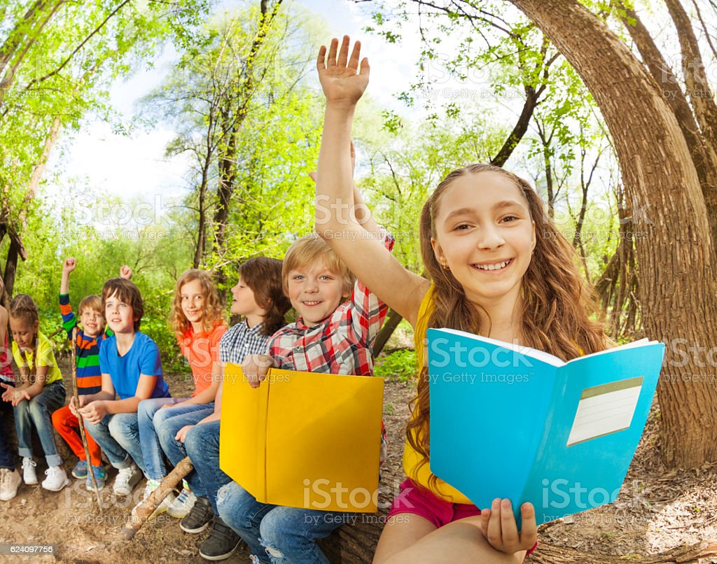 Happy kids reading books outdoor at sunny day stock photo