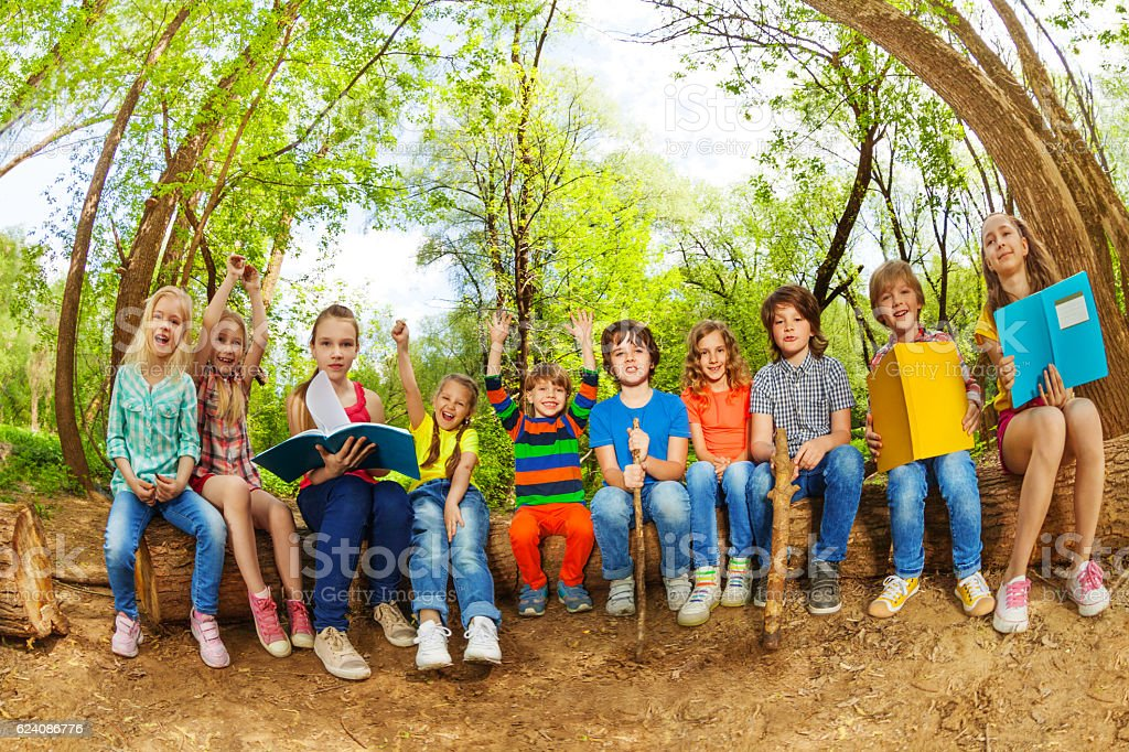 Happy kids reading books outdoor in summer camp stock photo