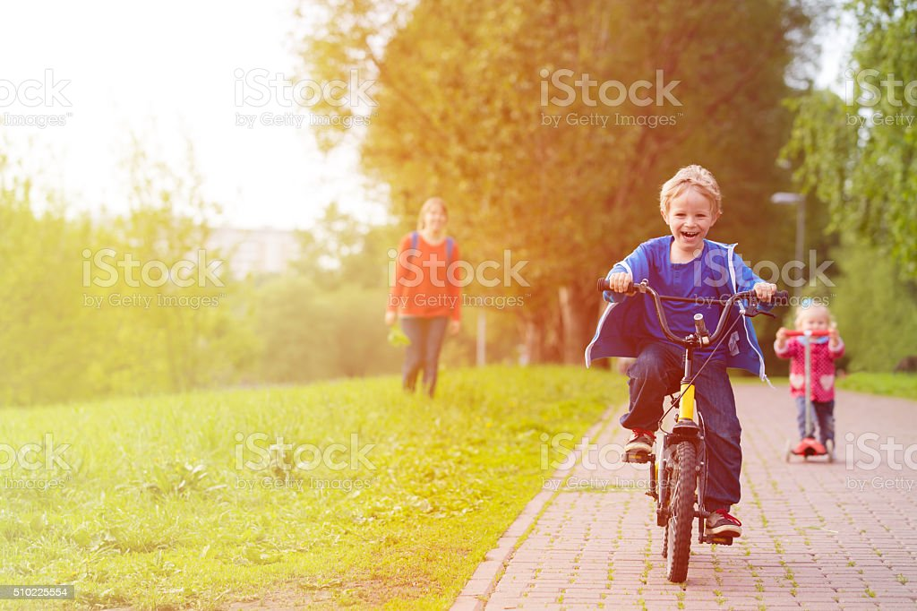 happy kids riding scooter and bike in the park stock photo