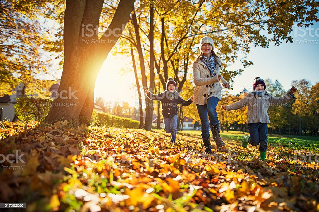 Happy kids running in park on sunny autumn day. stock photo