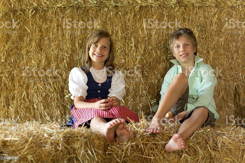 happy kids sitting in straw stock photo