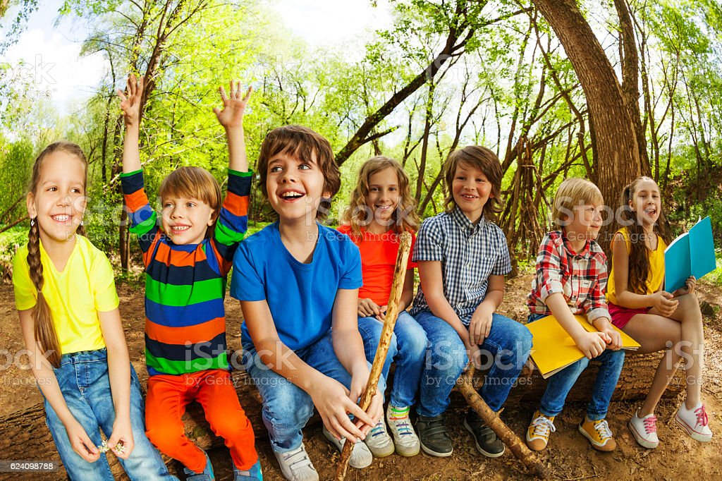 Happy kids sitting on a log and reading books stock photo