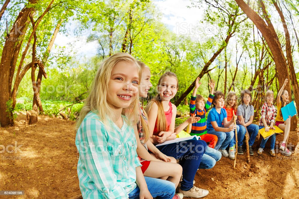 Happy kids sitting on a log in the summer camp stock photo