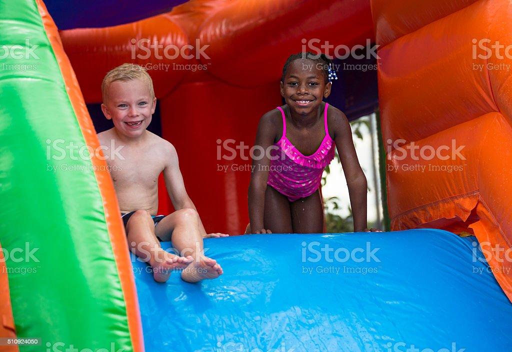 Happy kids sliding down an inflatable bounce house stock photo
