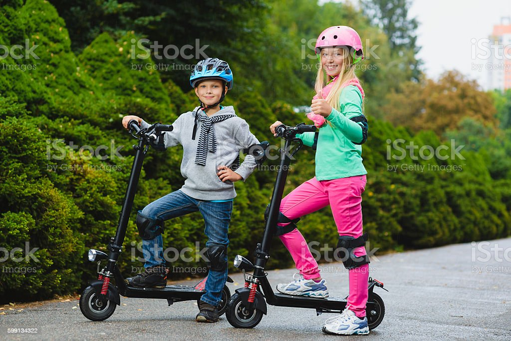 Happy kids standing on electric scooter outdoor stock photo