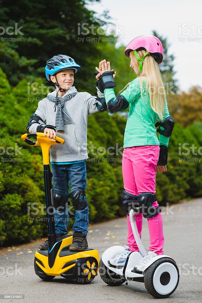 Happy kids standing on hoverboard or gyroscooter outdoor stock photo