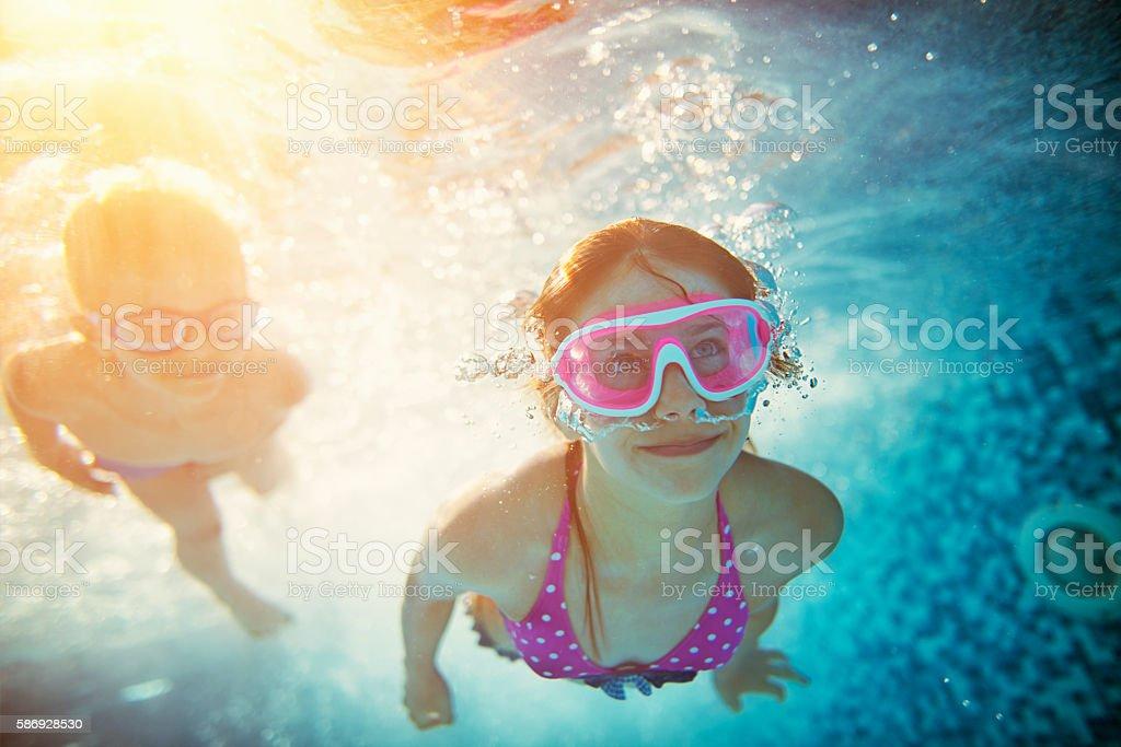 Happy kids swimming underwater in pool stock photo