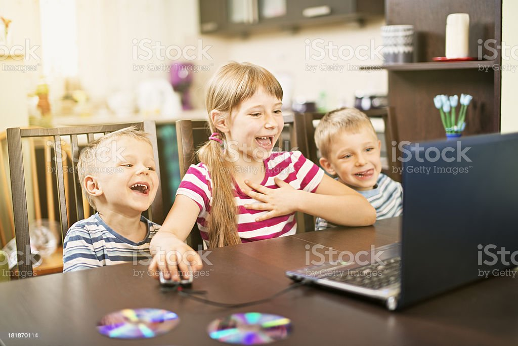 Happy kids using  laptop stock photo