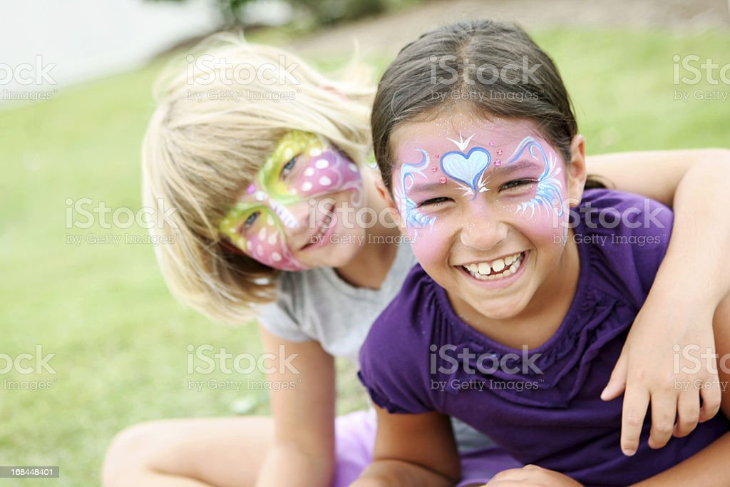 Happy kids with painted faces wearing purple stock photo