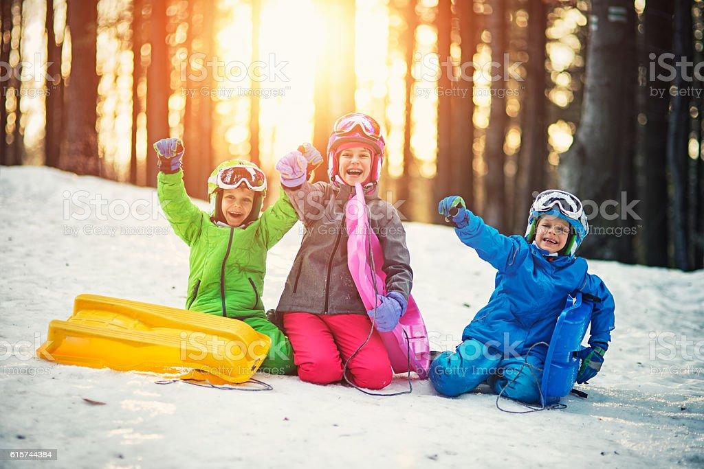 Happy kids with toboggans enjoying winter stock photo