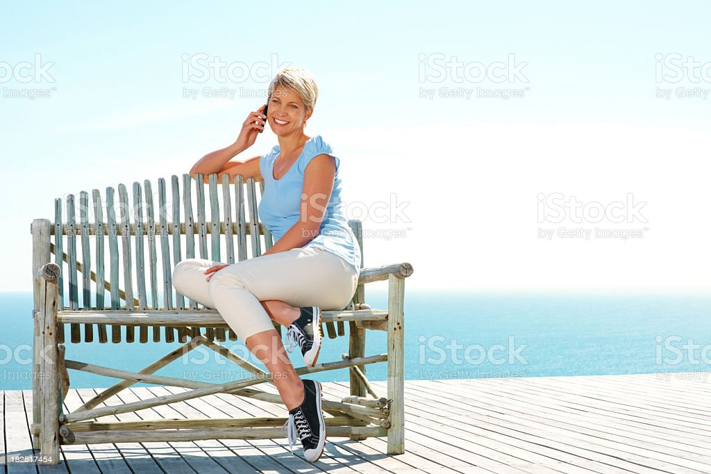 Happy lady using a cellphone while sitting on bench royalty-free stock photo