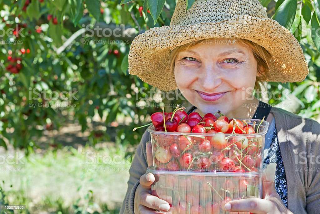 Happy lady with cherries under a cherry tree stock photo