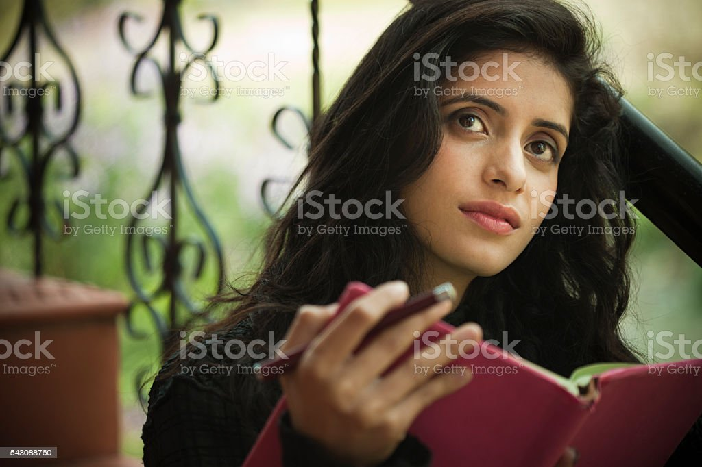 Happy late teen girl student thinking while holding a book. stock photo