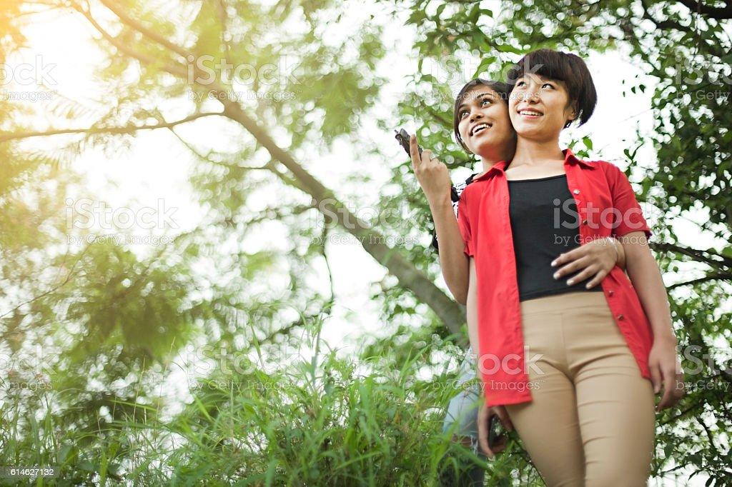 Happy late teen multi ethnic female friends enjoying in nature. stock photo