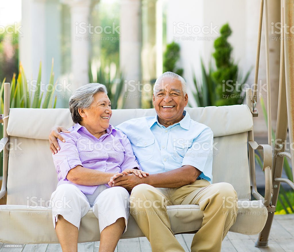 Happy latin couple sitting on swing stock photo
