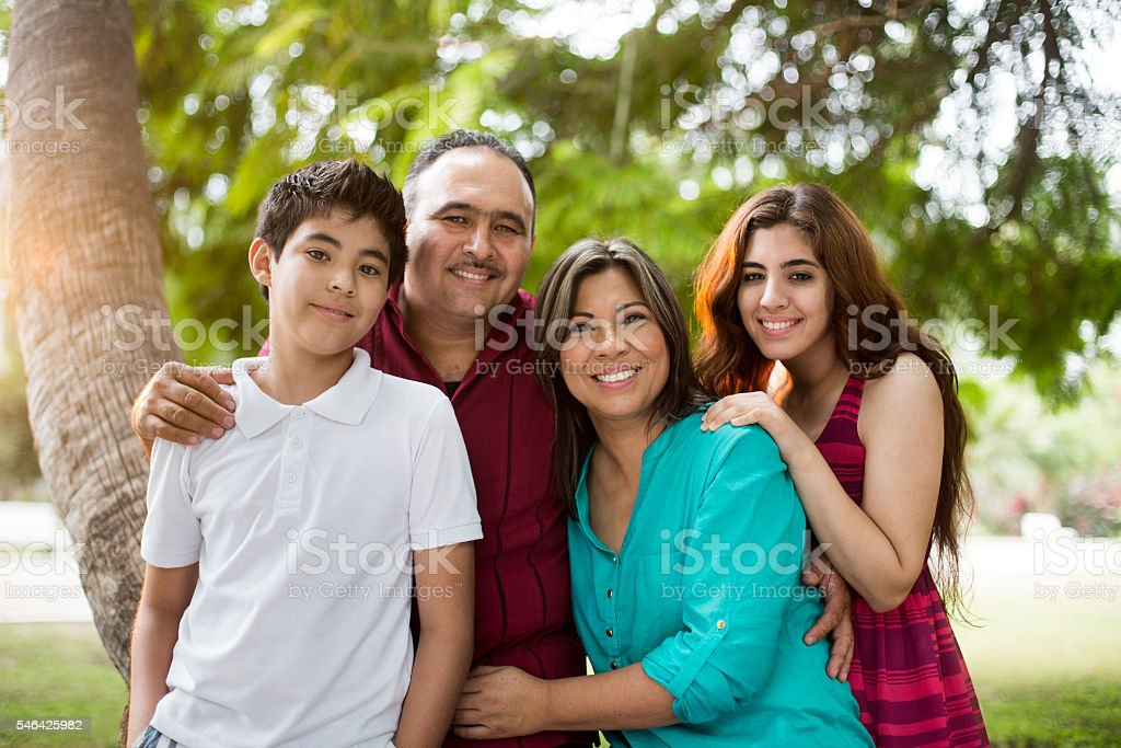 Happy latin family smiling and standing next to tree stock photo