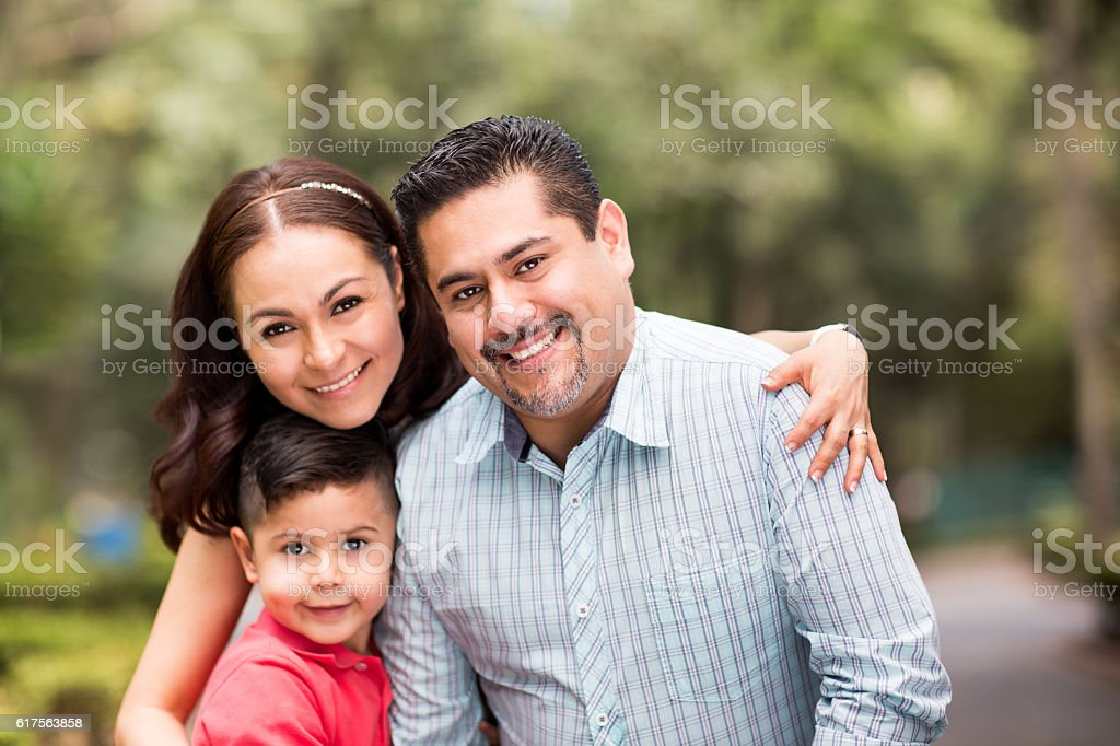 Happy latin family with one child smiling at camera stock photo