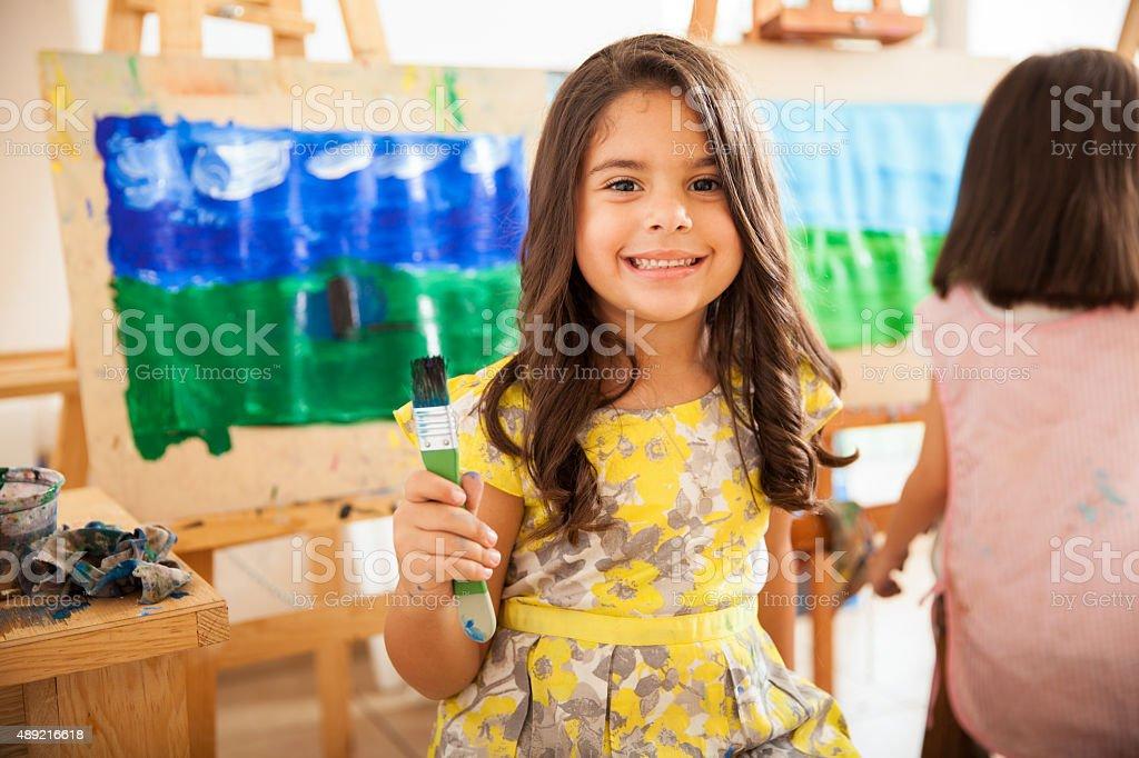 Happy Latin girl in art class stock photo