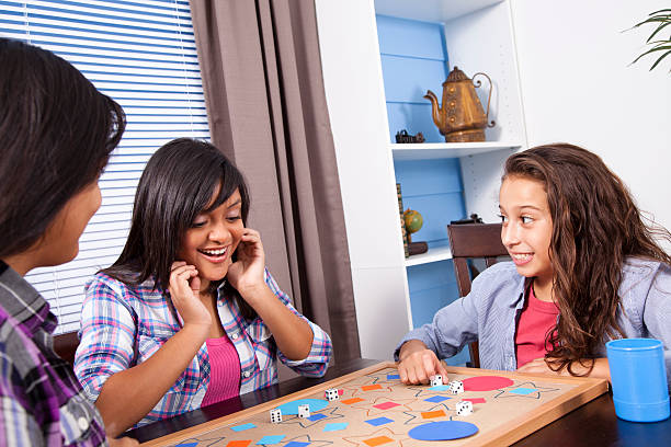 Group Of Friends Playing Dice Game In Family Living Room Pictures