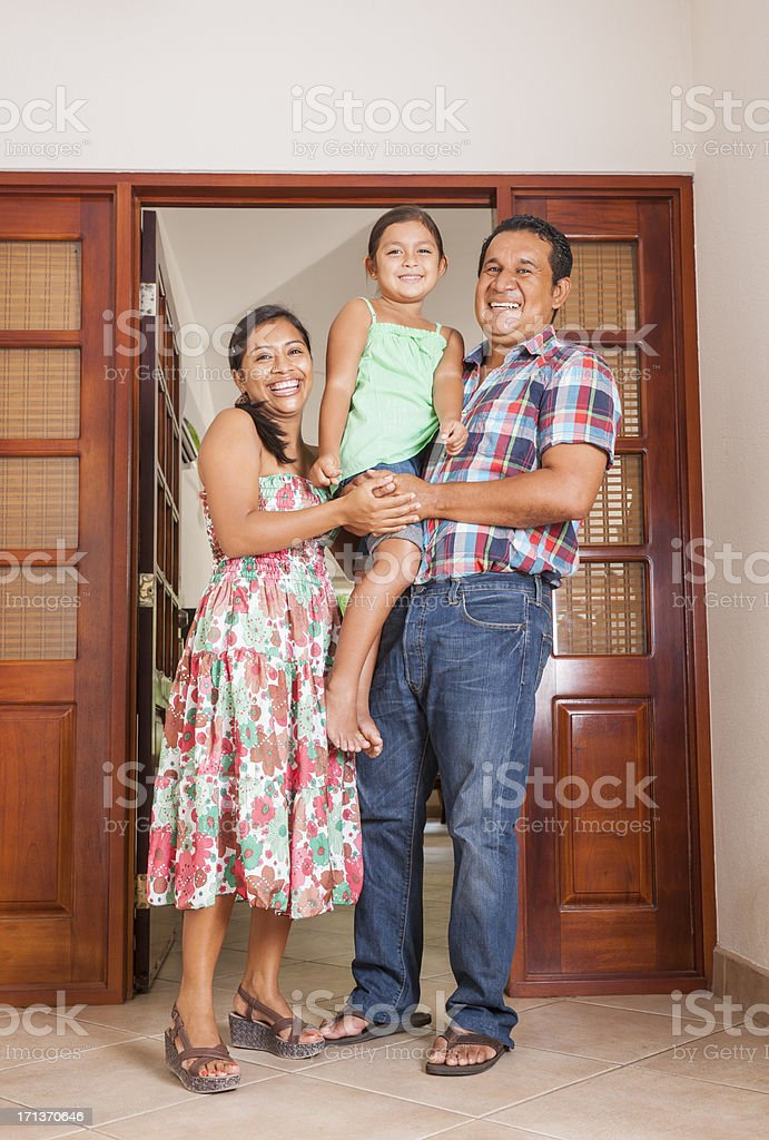 Happy Latino family in the doorway of their home royalty-free stock photo