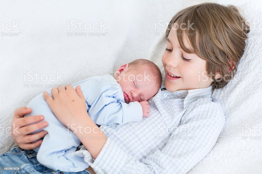 Happy laughing boy holding his sleeping newborn baby brother stock photo