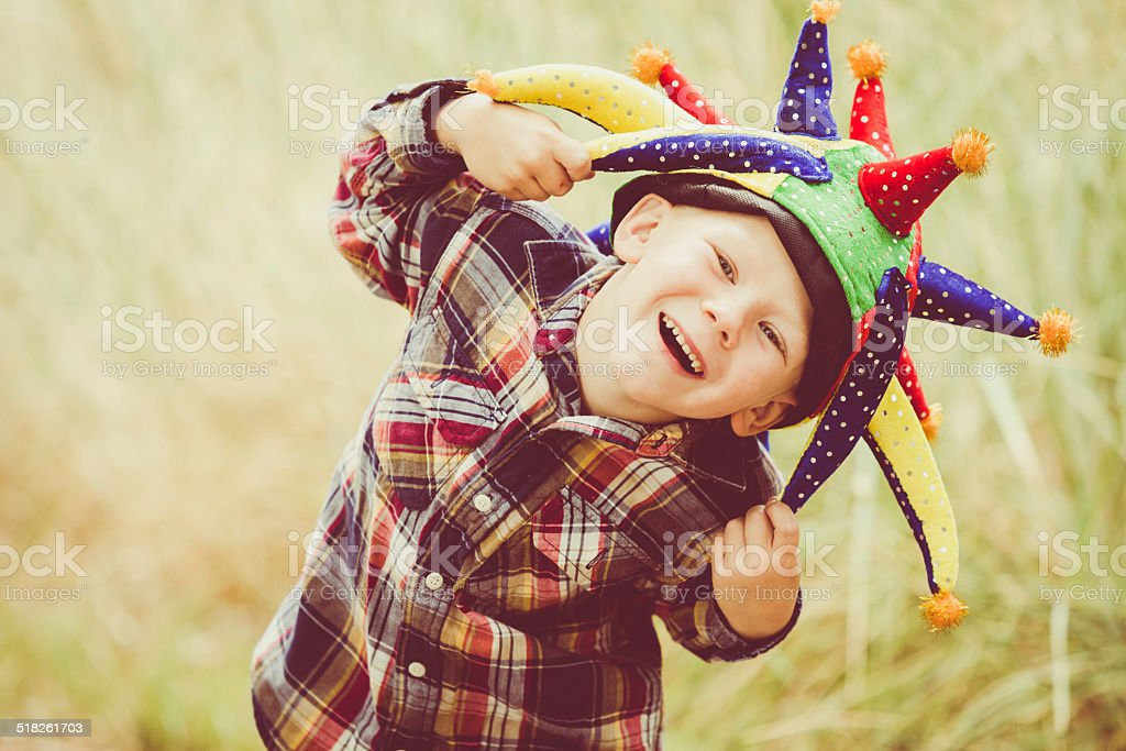 Happy Laughing Boy Playing & Wearing Joker Hat Outdoors stock photo