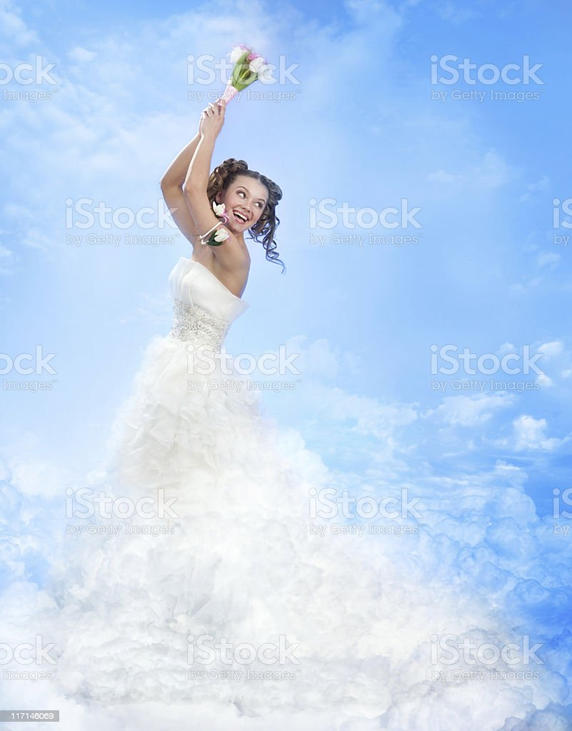 Happy Laughing Bride Throwing a Bowquet in the Sky. royalty-free stock photo