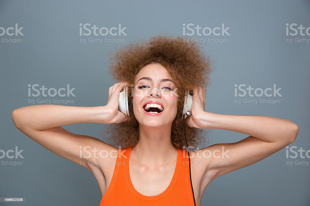 Happy laughing curly girl listening to music using headphones stock photo