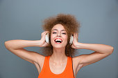 Happy laughing curly girl listening to music using headphones