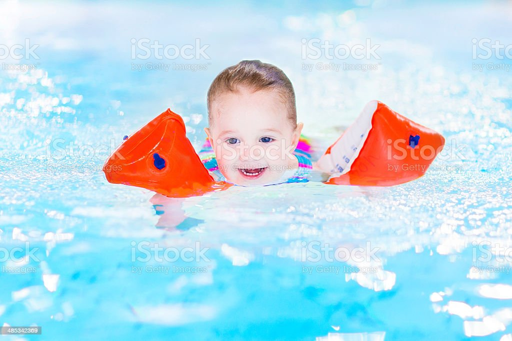 Happy laughing toddler girl having fun in a swimming pool stock photo