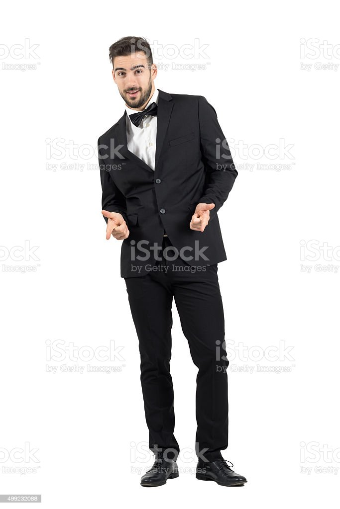 Happy laughing young luxurious man in tuxedo pointing at camera stock photo