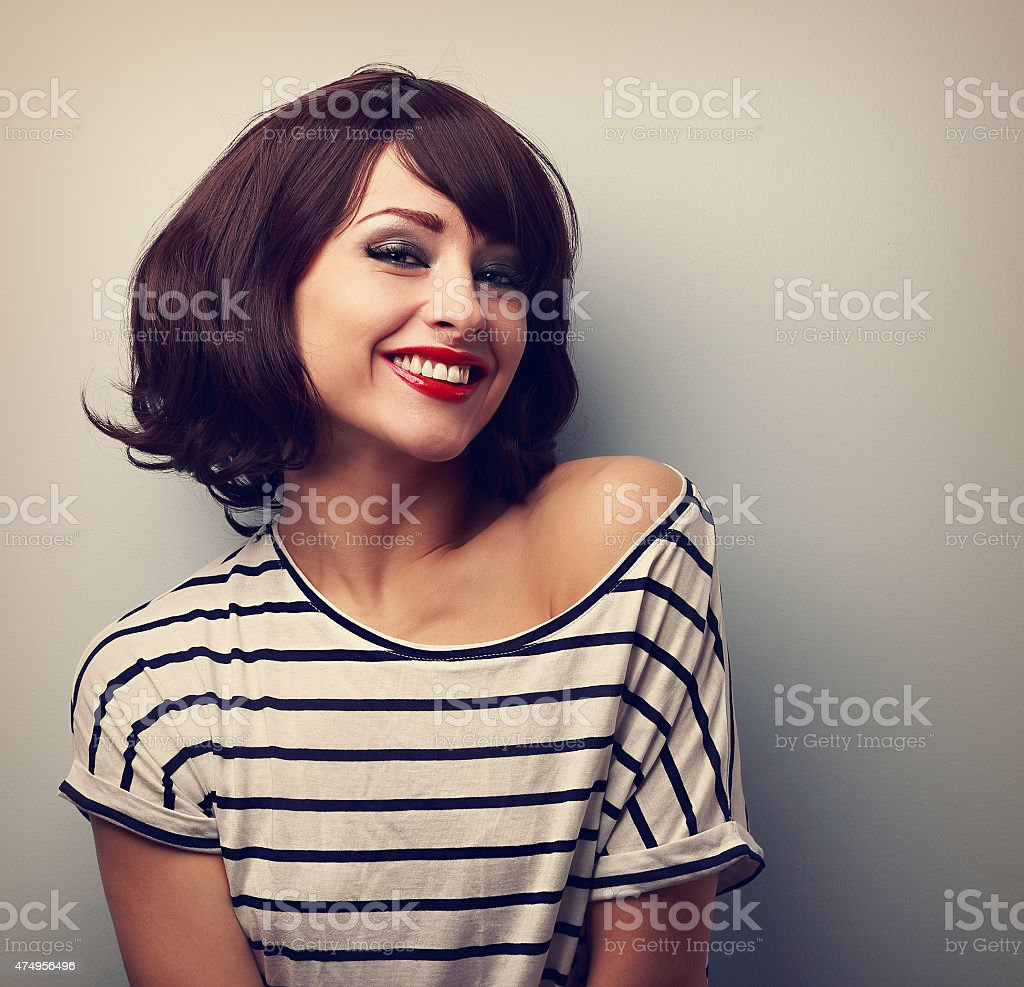 Happy laughing young woman with short hair in fashion blouse stock photo