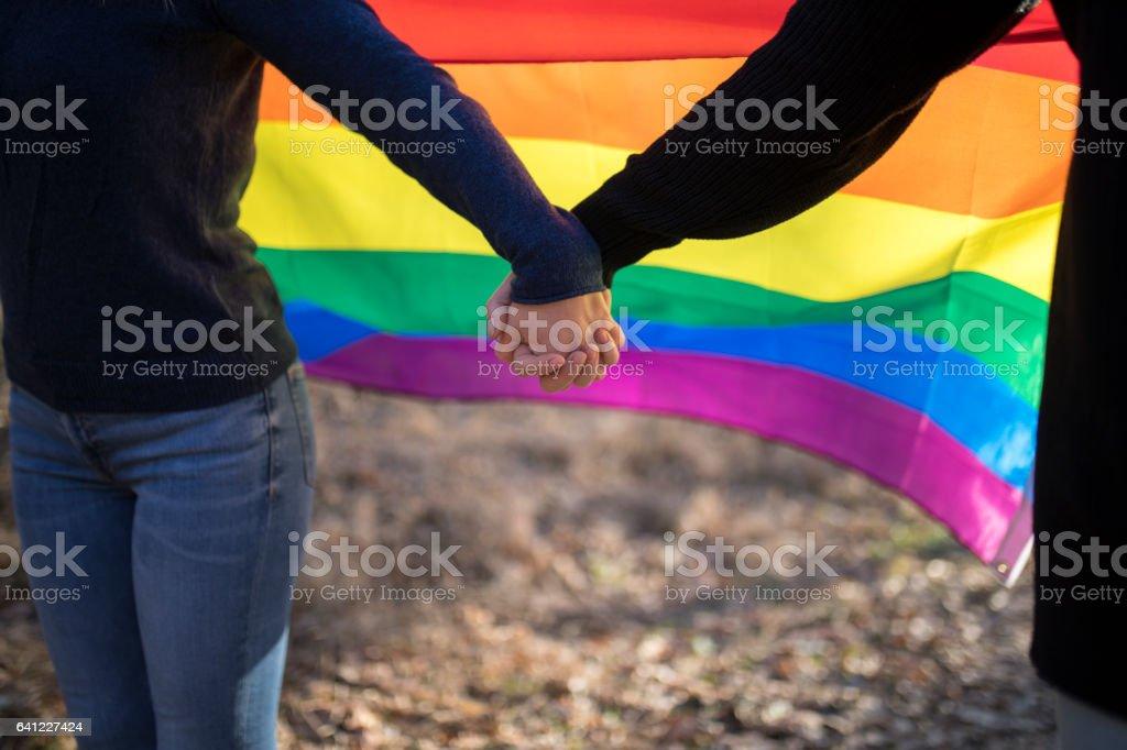 Happy lesbian couple holding hands over rainbow flag background stock photo