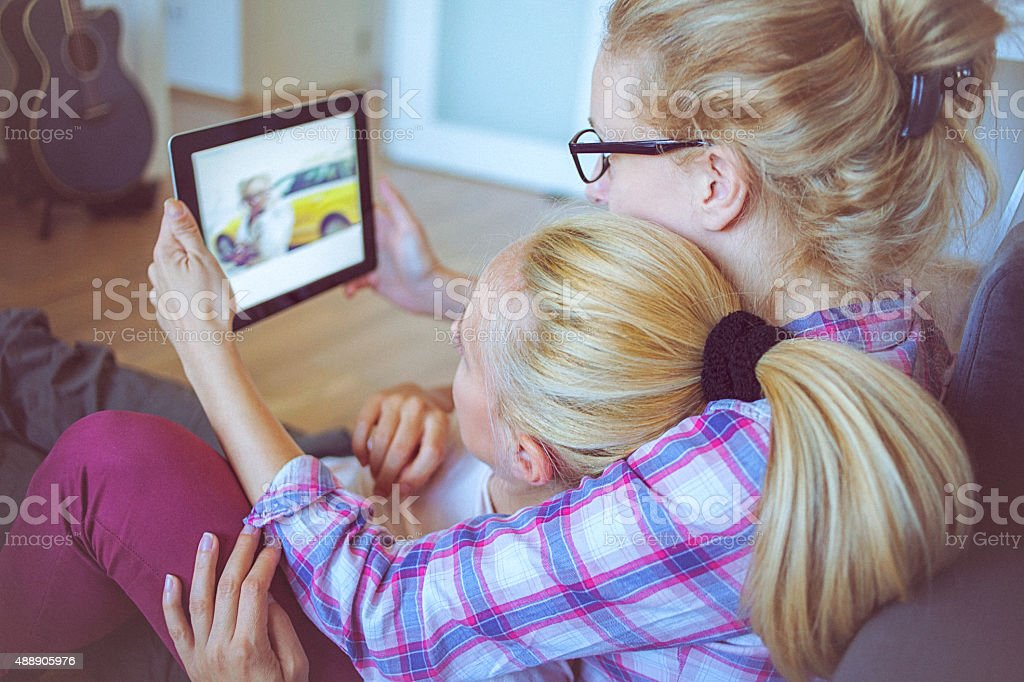 Happy lesbian couple in love embraced using digital tablet stock photo