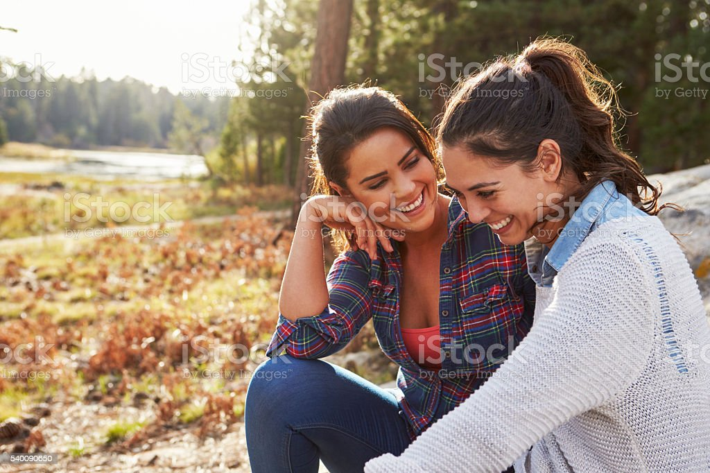 Happy lesbian couple laughing together in the countryside stock photo