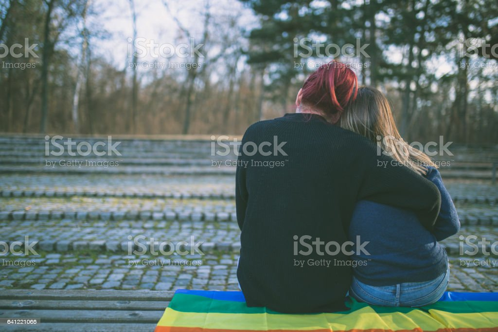 Happy lesbian couple sitting on the bench in park stock photo