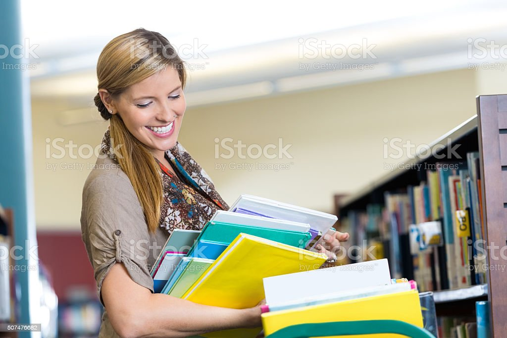 Happy librarian putting books away in school library stock photo