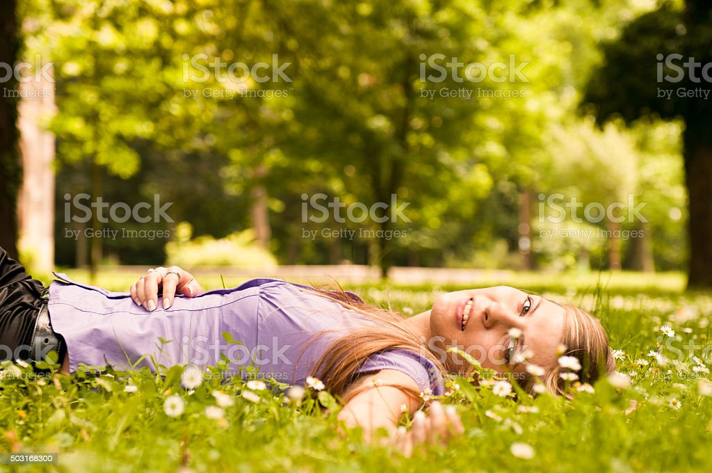 Happy life - lying in grass with flowers stock photo