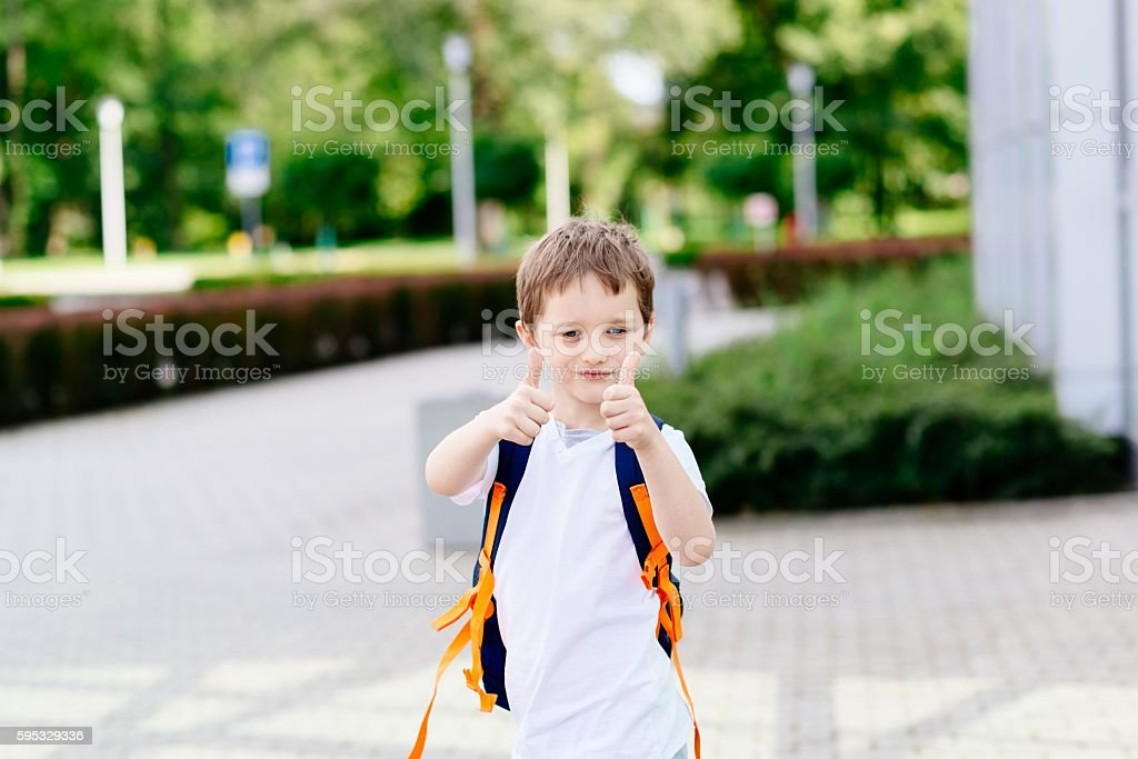 Happy little 7 years schoolboy showing thumbs up stock photo