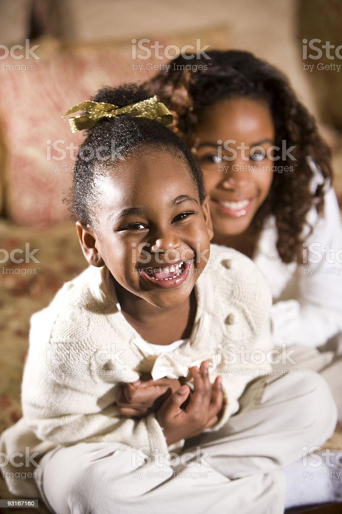 Happy little African American girl with big sister stock photo