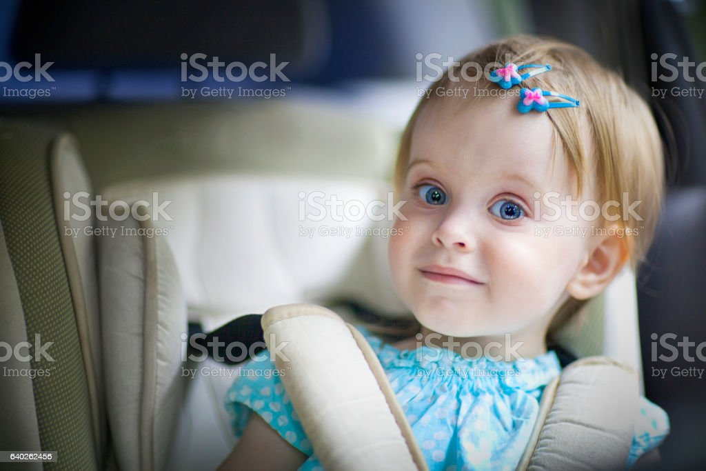 Happy little baby girl in the car seat stock photo