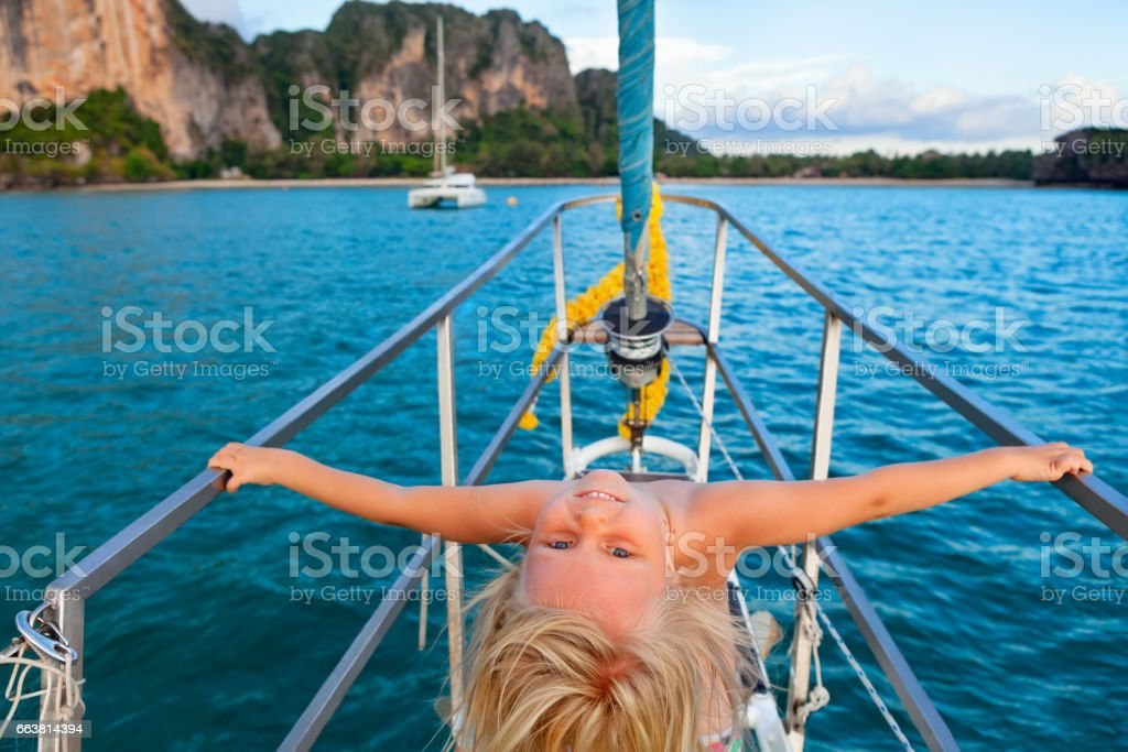 Happy little baby girl on board of sailing yacht stock photo