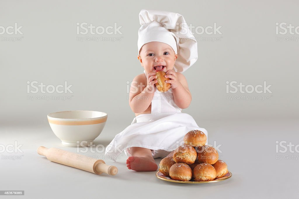 Happy little baby in a cook cap laughs stock photo