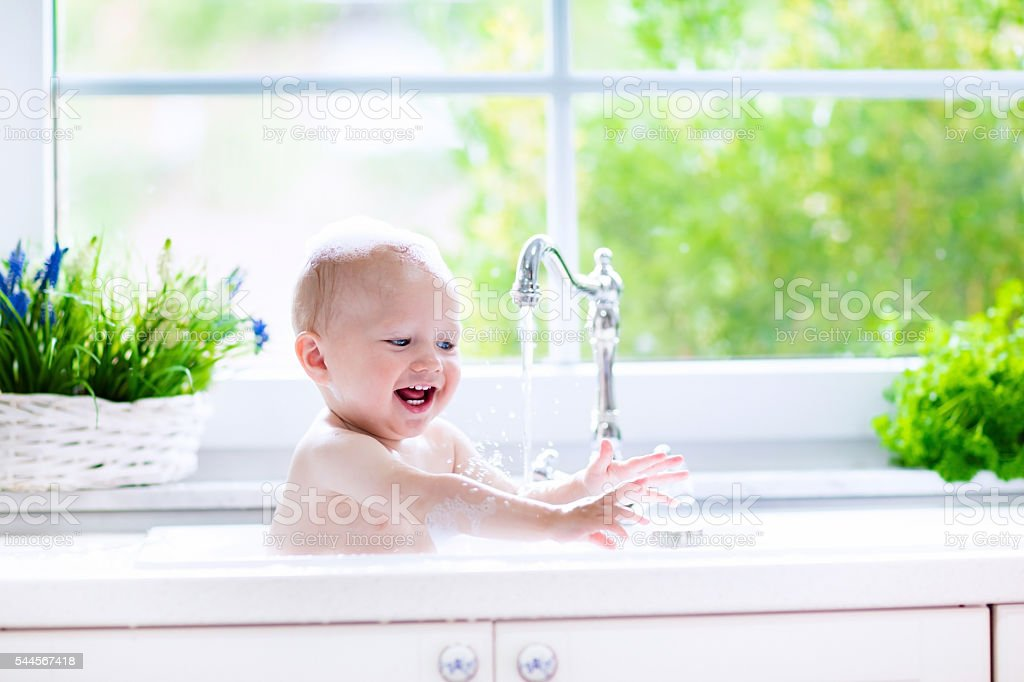 Happy little baby taking bath stock photo