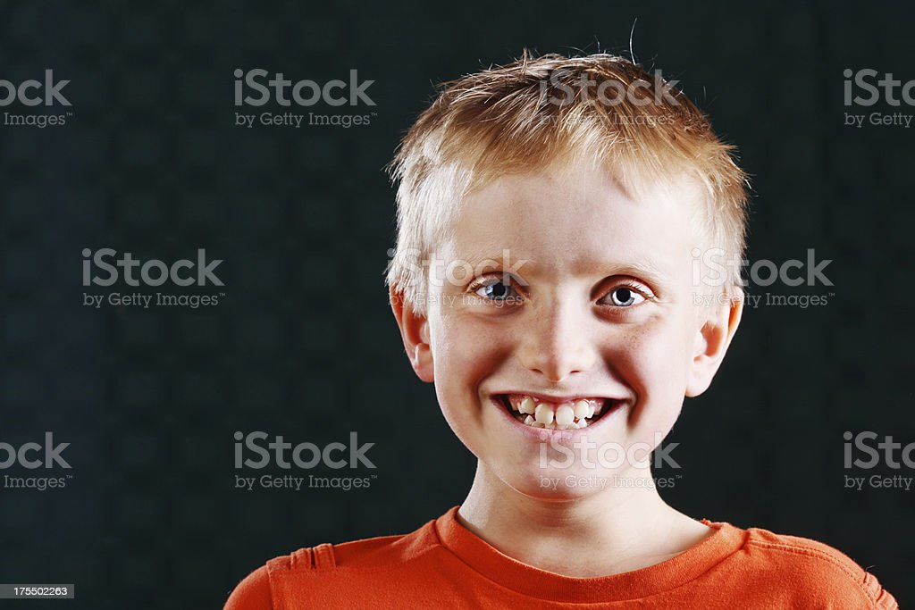 Happy little blond boy laughing against black royalty-free stock photo