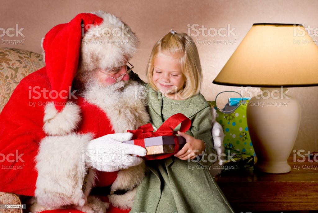Happy little blond girl receives a gift from Santa royalty-free stock photo