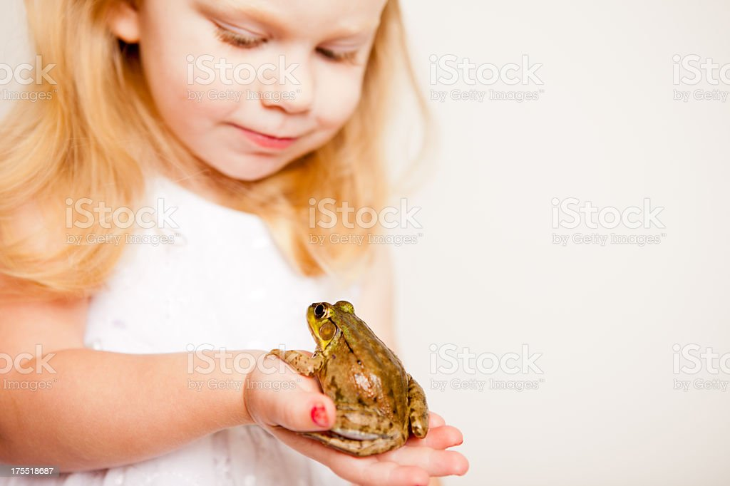 Happy Little Blond Princess Holding a Frog, With Copy Space stock photo